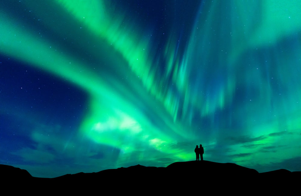 See the Northern Lights: Couple admiring the Northern Lights